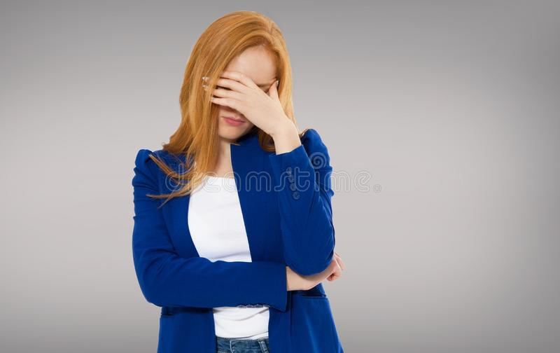 Woman head pain, Female migraine, Unhappy Young Adult Female Wearing Blouse, Hitting Her Head, Eyes Closed, Gesturing She Has Made royalty free stock image