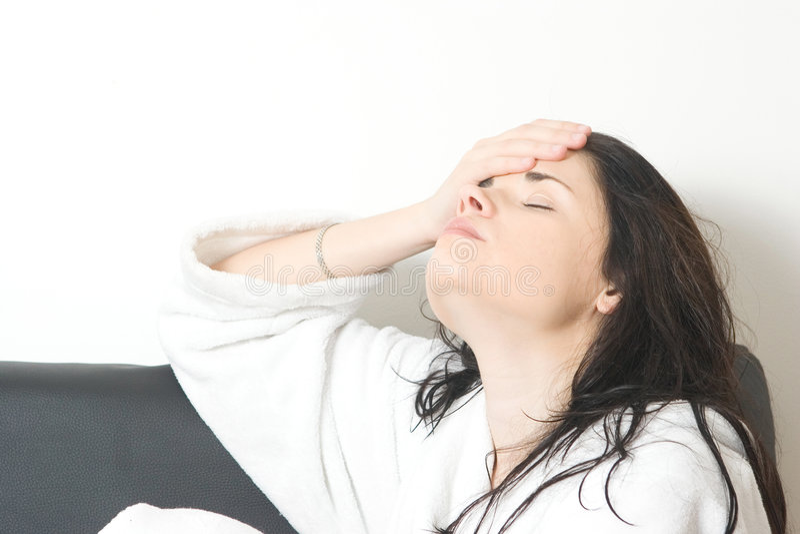 Woman with headache. Beautiful woman after a bath having a headache stock image