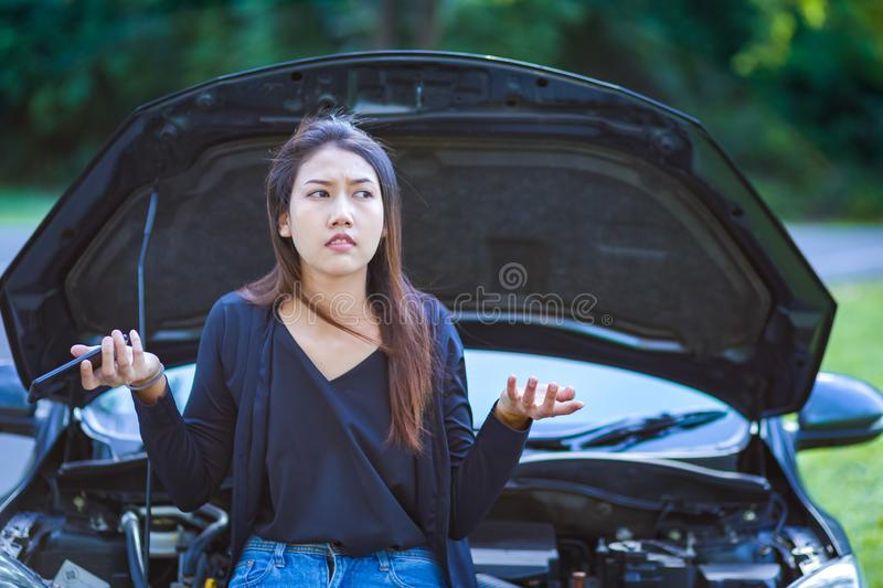 A woman headache while looking at broken down car on road royalty free stock photo