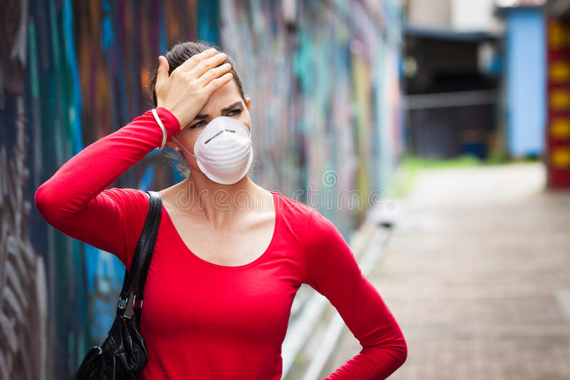 Woman with headache wearing a face mask royalty free stock images