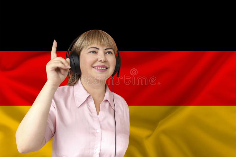 Woman in headphones on a background of the colored flag of the Federal Republic of Germany on the texture of the fabric, silk with stock images
