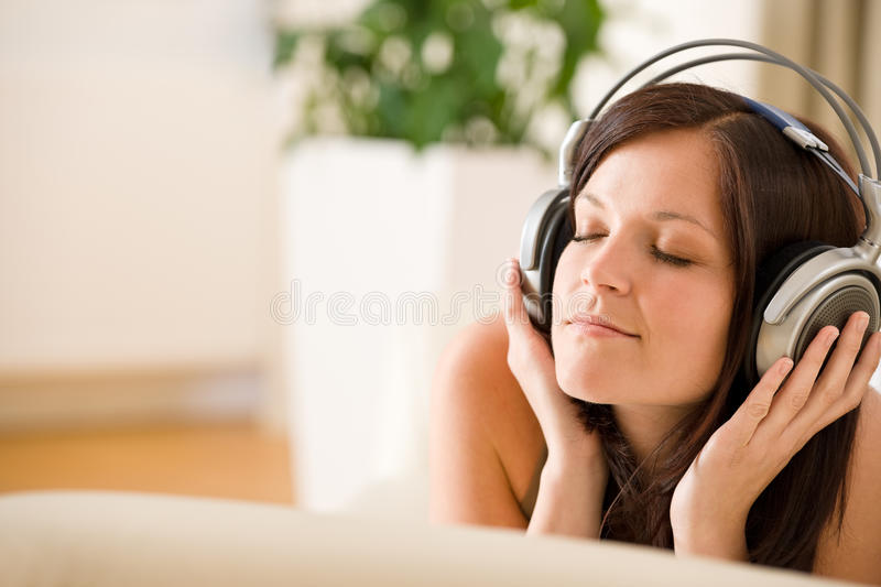 Woman with headphones listen to music in lounge stock image