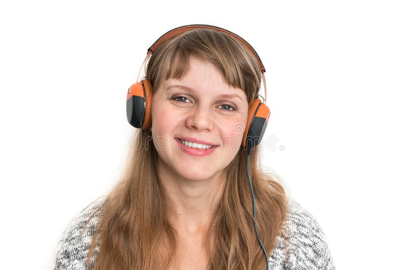 Woman with headphones is listening rock music. Pretty woman with headphones is listening rock music royalty free stock photo