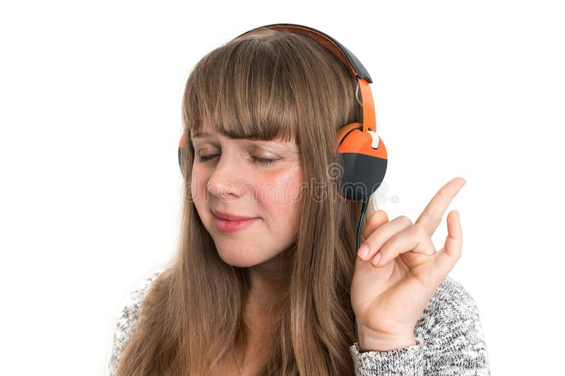 Woman with headphones is listening rock music. Pretty woman with headphones is listening rock music stock images