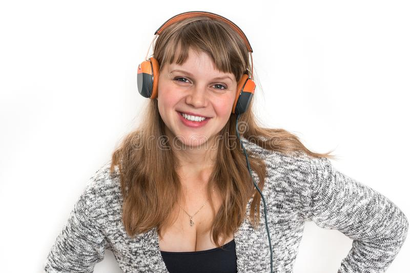 Woman with headphones is listening rock music. Pretty woman with headphones is listening rock music stock photo