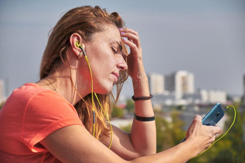 Woman with headphones on, listening to a song on her phone and looking sad with her eyes closed.  stock image