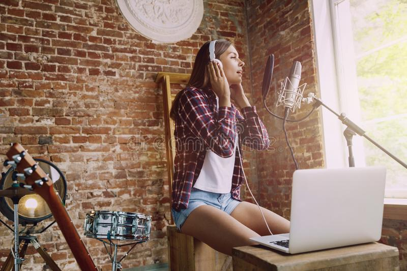 Woman recording music, broadcasting and singing at home. Woman in headphones recording music video blog home lesson, singing or making broadcast internet royalty free stock photos