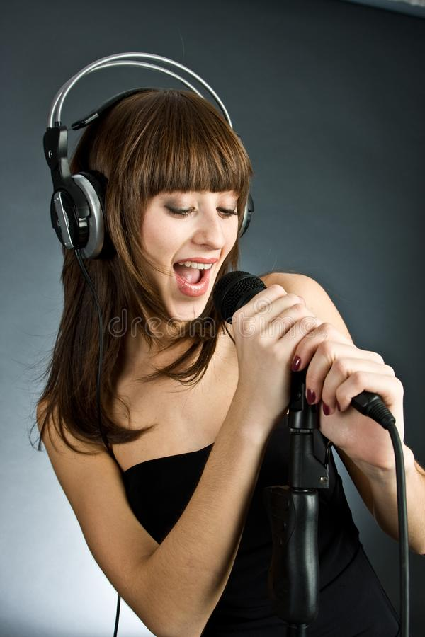Woman in headphones Singing into Microphone stock photo