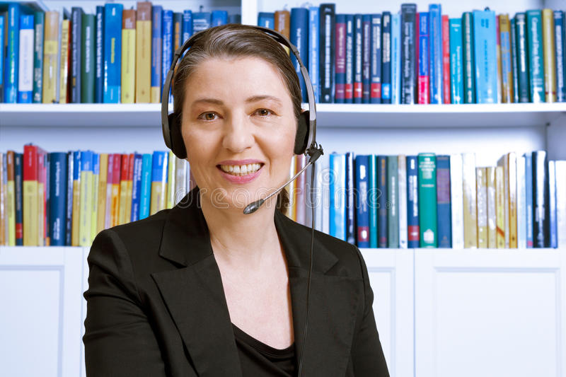 Woman headset legal financial advice. Friendly smiling middle aged woman with headset and black blazer in an office with lots of books, lawyer or accountant royalty free stock image