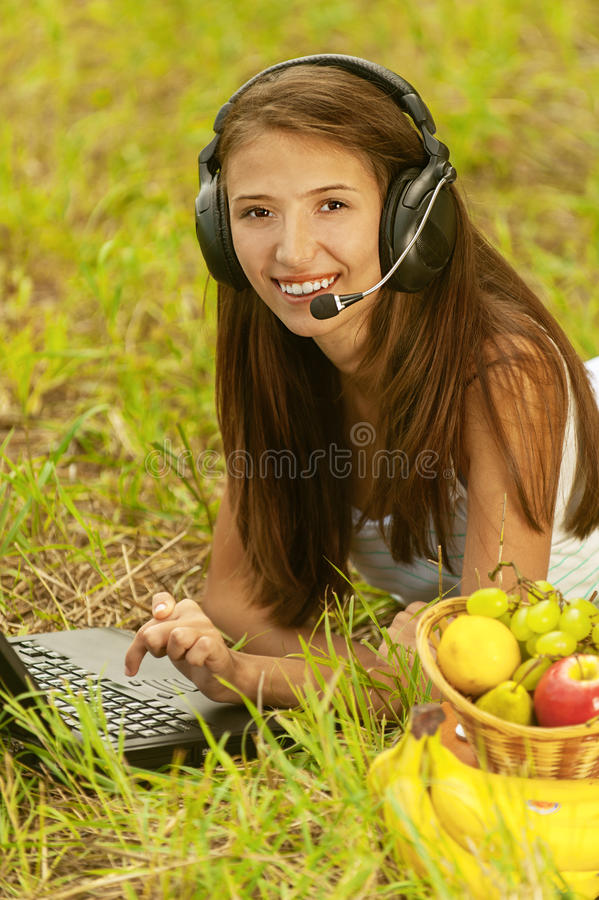 Woman With Headset Lie On Grass Stock Photography