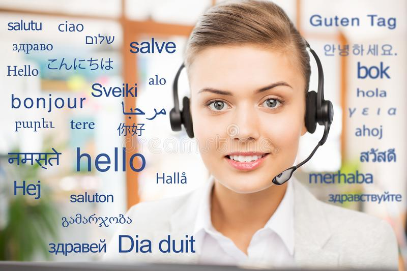 Woman in headset over words in foreign languages. Translation, business and technology concept - smiling female translator or operator in headset at office over stock images