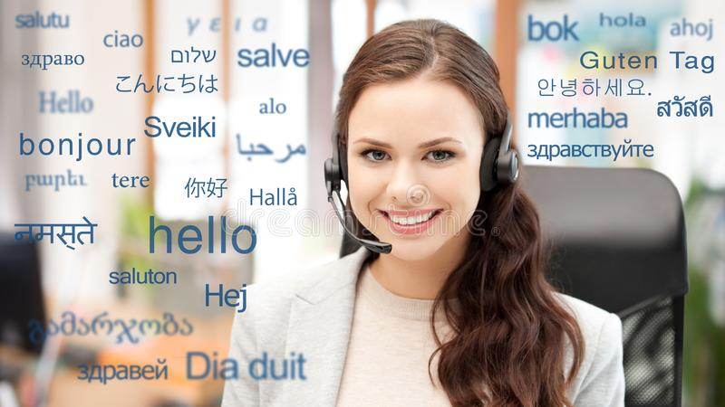 Woman in headset over words in foreign languages. Translation, business and technology concept - smiling female translator or operator in headset at office over stock image