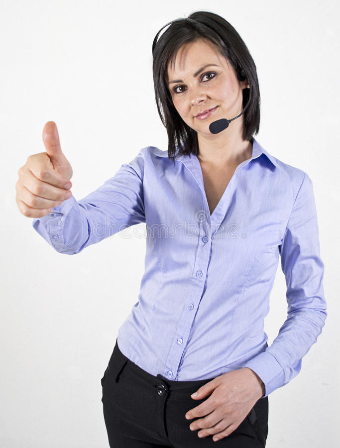 Woman with headset showing thumbs up. A woman with a telephone hands free headset showing a thumbs up sign royalty free stock photo