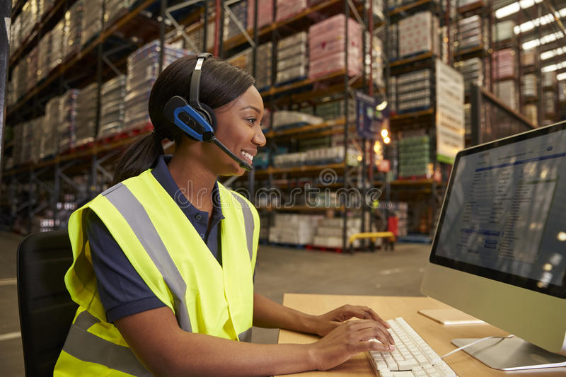 Woman with headset working in on-site office of a warehouse royalty free stock photo