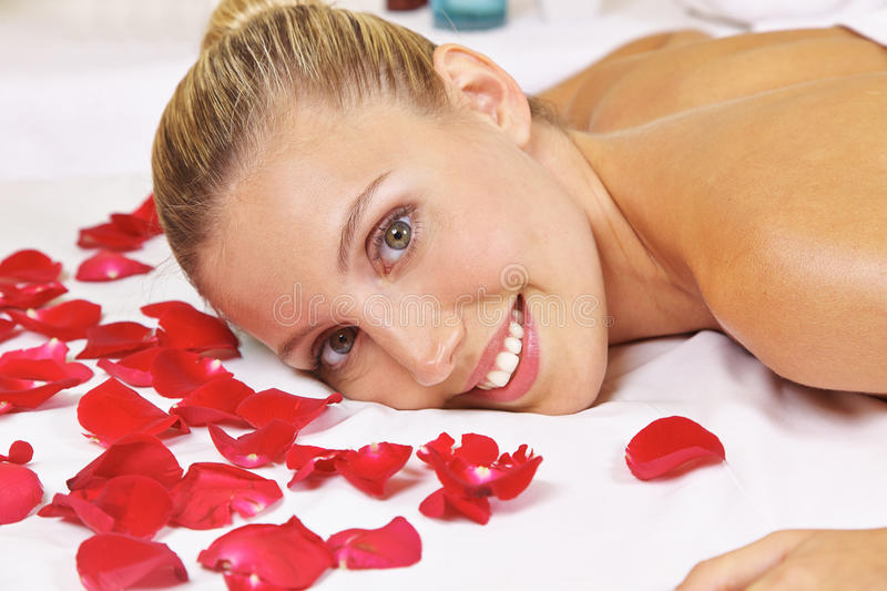 Woman in health resort spa. Smiling young woman laying in health resort spa with rose petals stock photo