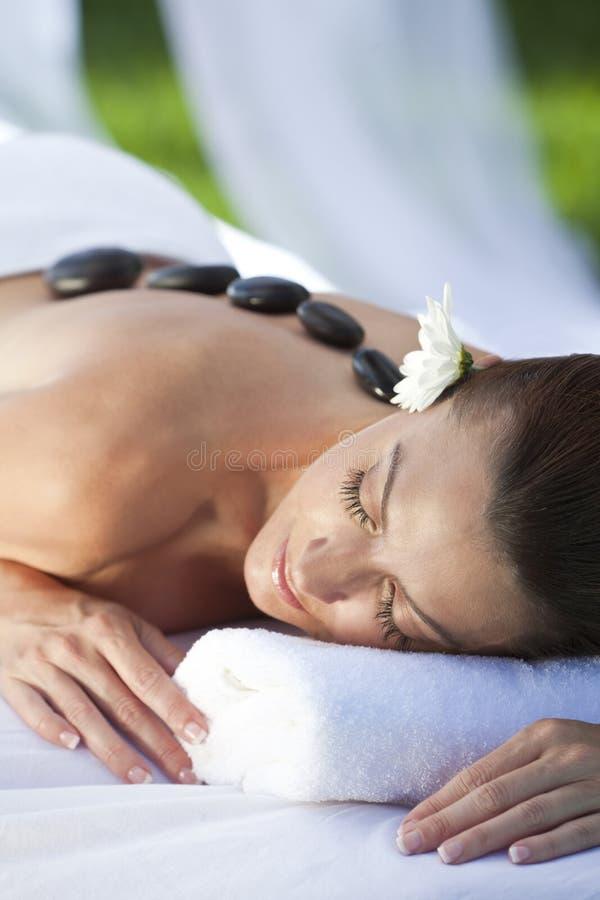 Woman At Health Spa Having Hot Stone Treatment Royalty Free Stock Photos