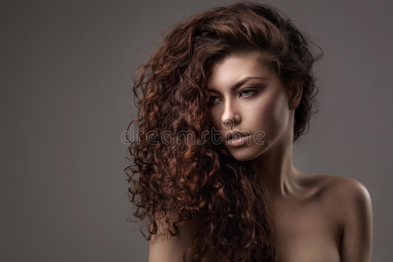 Woman with healthy brown curly hair stock image