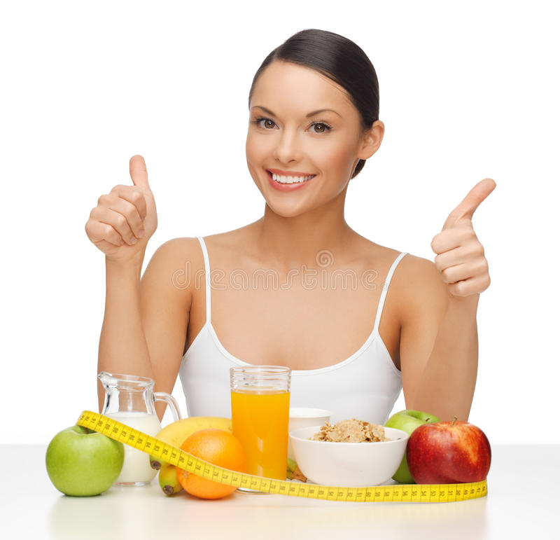 Woman with healthy food. Beautiful woman with healthy food showing thumbs up royalty free stock photos
