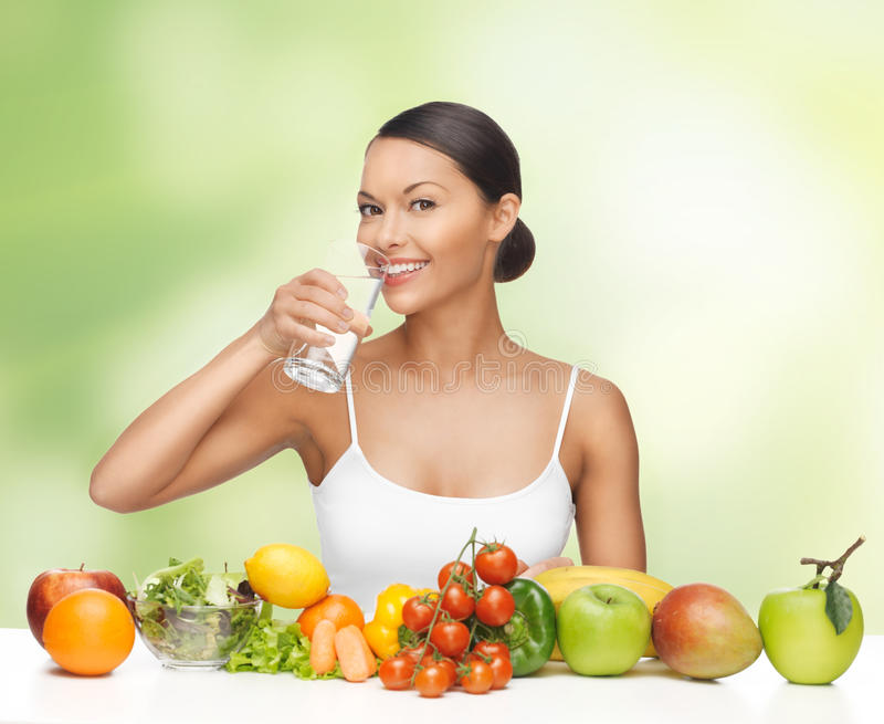Woman with healthy food. Beautiful woman with healthy food and water royalty free stock image