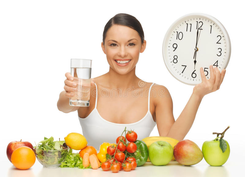 Woman with healthy food. Beautiful woman with healthy food water and clock stock photos