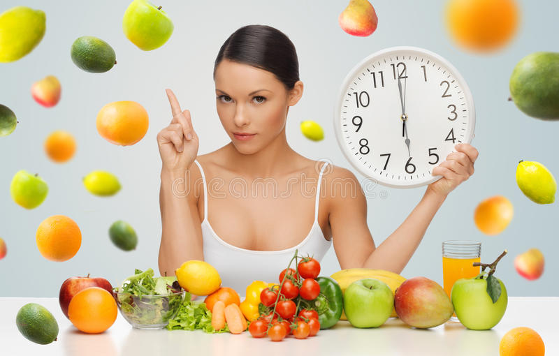 Woman with healthy food and clock warning. People, eating and diet concept - woman with healthy food holding big clock, pointing finger up and warning over gray royalty free stock photo
