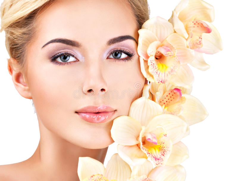 Woman with healthy skin and flowers close to face stock photography