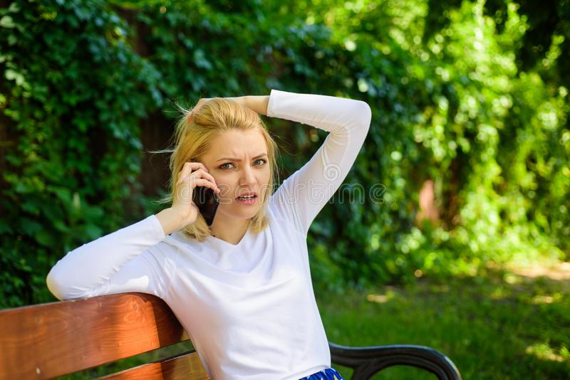 Woman heard bad news. Bad news. Girl blonde tense face talk smartphone green nature background. Woman having mobile. Phone conversation in park. Girl modern stock images