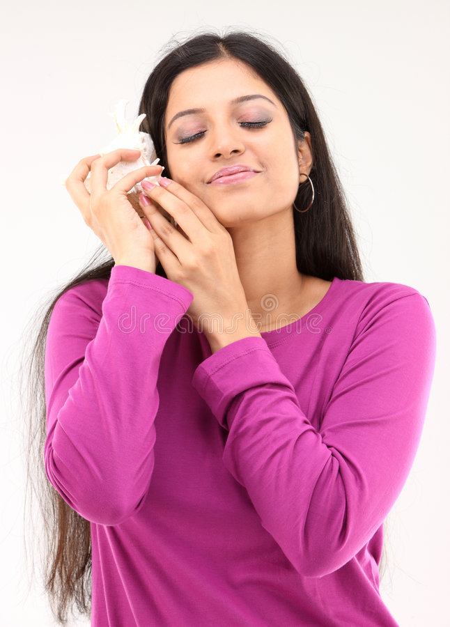 Woman hearing the sound from the shell royalty free stock photo