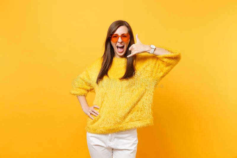 Woman in heart orange glasses doing phone gesture like says: call me back with hand and fingers like talking on the. Telephone isolated on yellow background stock photos