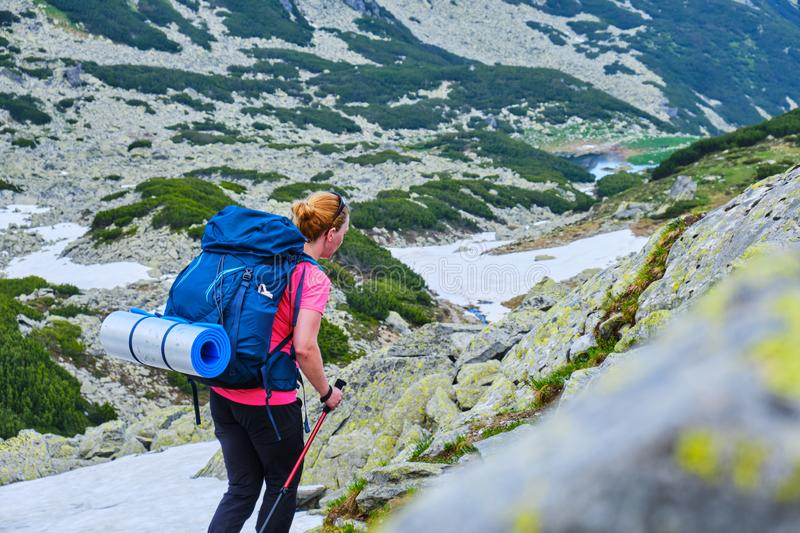 Woman with heavy backpack and a rolled sleeping pad, navigating a trekking trail in Retezat mountains part of Carpathians. royalty free stock photo