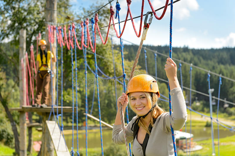 Woman climbing on rope ladder adrenalin park. Woman in helmet climbing on rope ladder in adrenalin park stock images