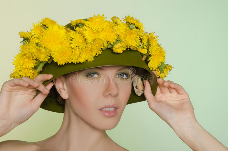 Woman in helmet with a wreath of dandelions. Woman in helmet with a wreath of yellow dandelions royalty free stock image
