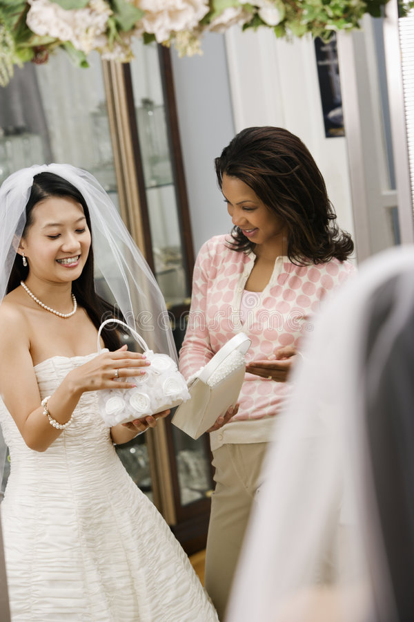 Woman helping bride. African-American woman helping Asian bride pick out handbag royalty free stock image