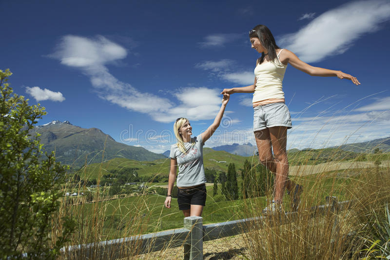 Woman Helping Friend Walk On Fence stock image