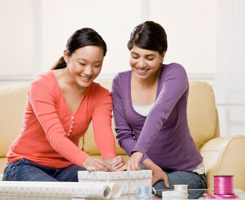 Woman helping friend wrap birthday gift. Woman helping generous friend wrap birthday gift royalty free stock photo