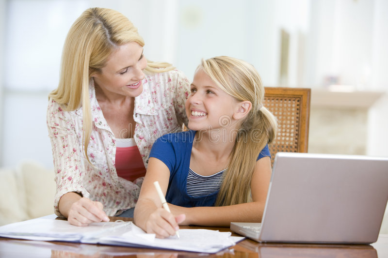 Woman helping girl with laptop doing homework