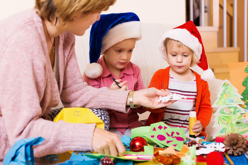 Woman helping girls to make decoration for Xmas. Woman helping little girls to make decoration for Xmas at home stock photo