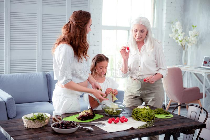 Grey-haired elderly woman helping her pregnant daughter cooking salad stock photos
