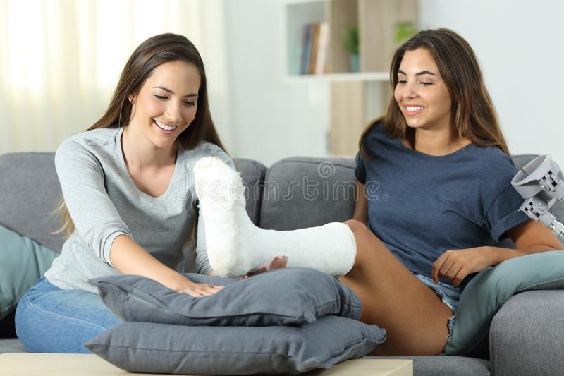 Woman helping her disabled friend. Happy women helping her disabled friend to be comfortable at home royalty free stock image