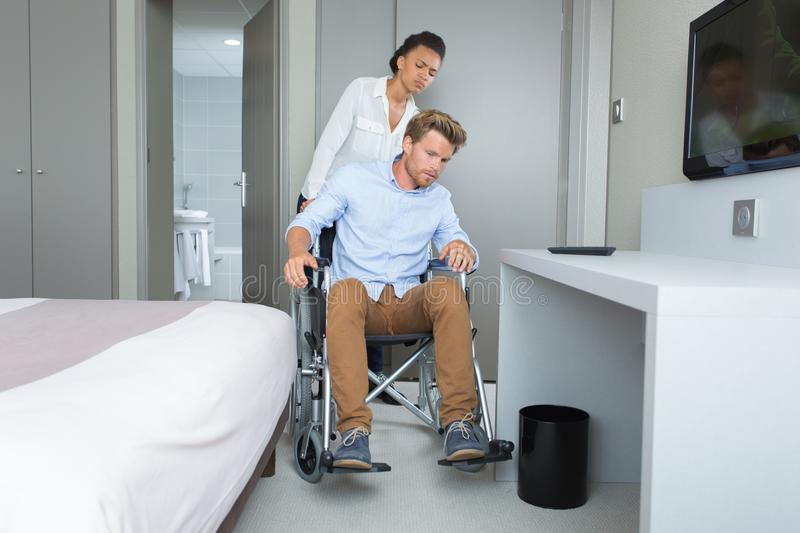 Woman helping partner on wheelchair stock photography