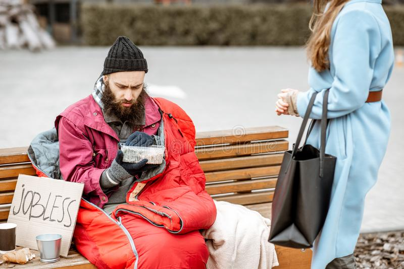 Woman giving food to a homeless beggar. Woman helping homeless beggar giving some food outdoors. Concept of helping poor people stock image