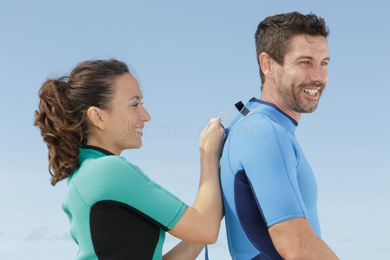Woman helping husband to zip up wetsuit stock photo