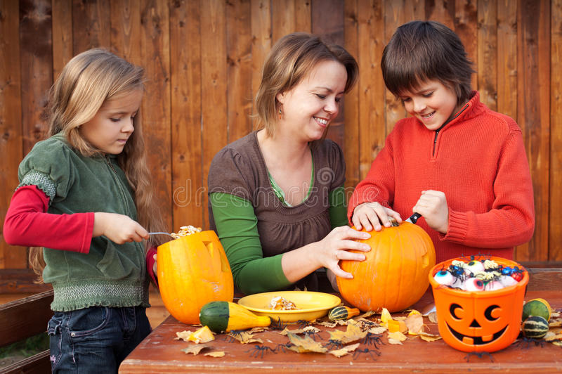 Woman helping kids to carve their Halloween jack-o-lantern. Woman helping kids to carve their pumpkin Halloween jack-o-lantern stock photos