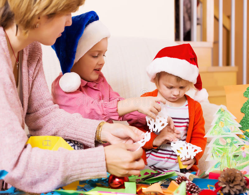 Woman helping little girls to make decoration for Xmas stock photos