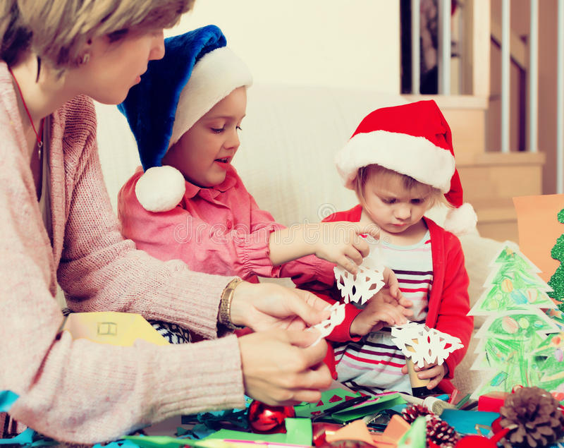Woman helping little girls to make decoration for Xmas. Young women helping little girls to make decoration for Xmas at home royalty free stock images