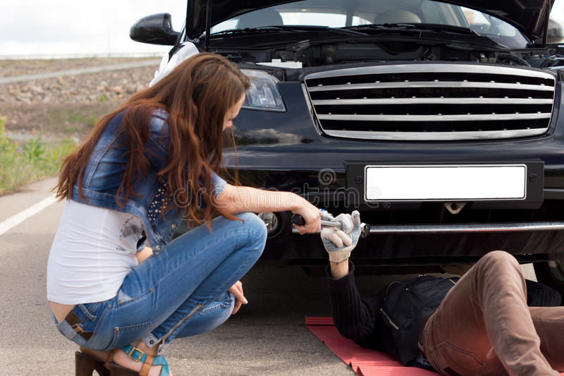 Woman helping a mechanic fix her car stock images