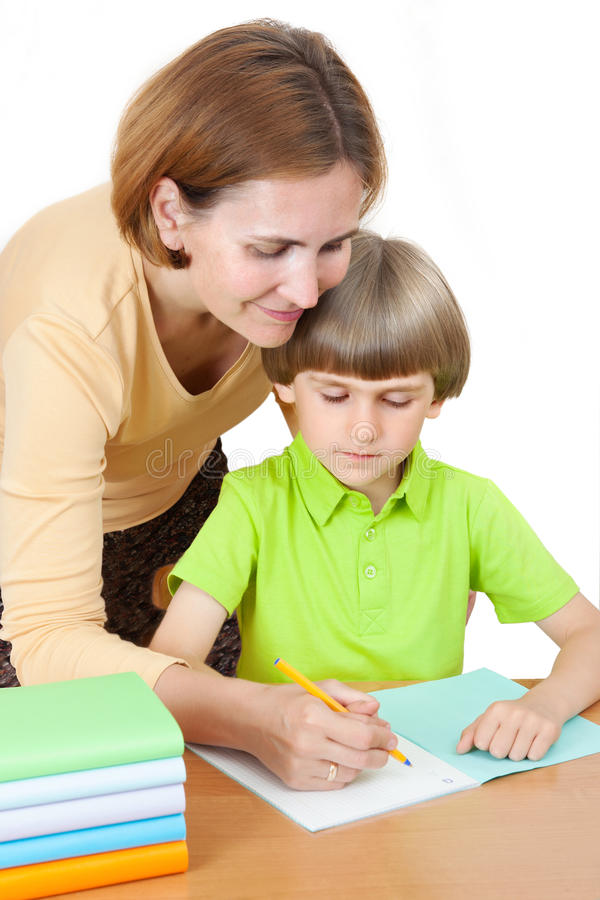 A woman helps first graders how to write in a notebook. A women helps first graders how to write in a notebook, isolated on white background stock images