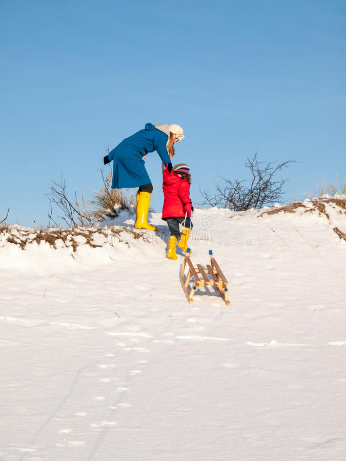 Woman helps girl pulling a sledge stock photo