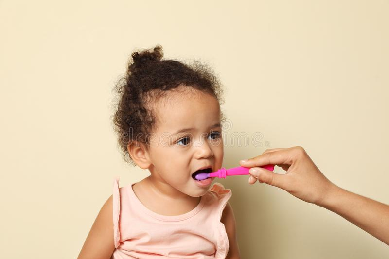 Woman and her African-American daughter with toothbrush stock image