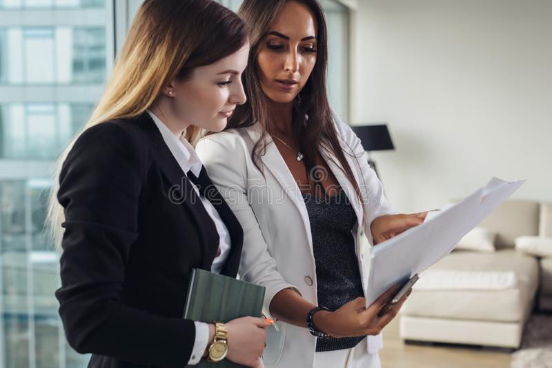 Woman and her assistant holding documents discussing business plan and strategy at workplace royalty free stock images